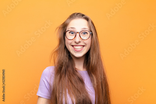 yound blonde woman looking happy and goofy with a broad, fun, loony smile and ey Canvas Print