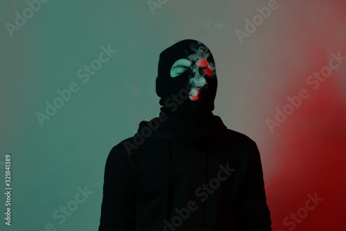 young man in hoodie and balaclava closing eyes and blowing smoke out Wallpaper Mural