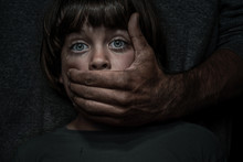 Child Abuse Concept. Portrait Of A Little Boy Hold By An Aggresive Adult