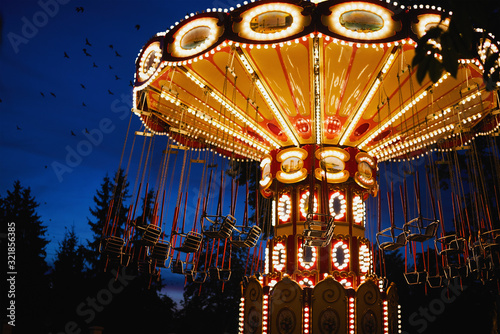 Photo Carousel Merry-go-round in amusement park at a night city