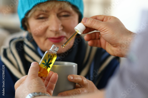 Fototapeta Elderly woman receives sedative drops from doctor. Close up an elderly woman looking at cup. Doctor collected carly hemp oil and drips them into patient cup. Prescription herbal drops. obraz