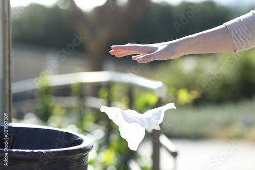 Hand throwing litter outside a bin in a park Fototapet