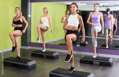 Fototapeta Sports young women performing step platform aerobics obraz