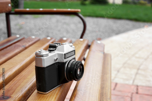 Obraz old camera on a bench on the street - fototapety do salonu