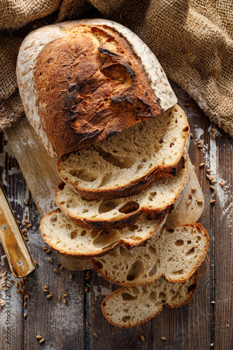 Fotomural Wheat and rye traditional sourdough bread cut into slices on a wooden board, top