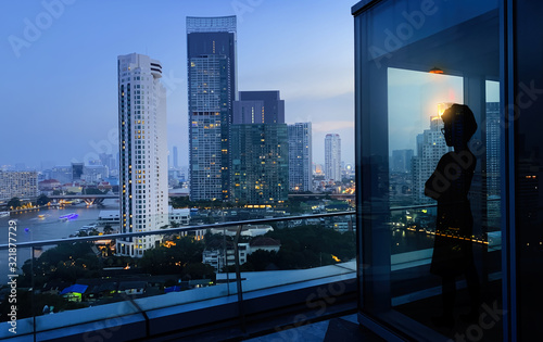 Silhouette of smart woman resting after late business meeting while standing near big office window city background