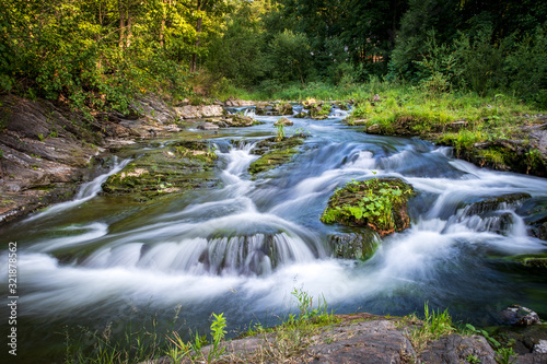 Fotomural Mountain forest stream in motion blur