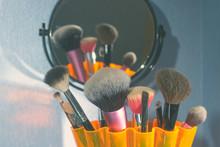 Make-up Brushes In A Orange Bowl On Blue Background