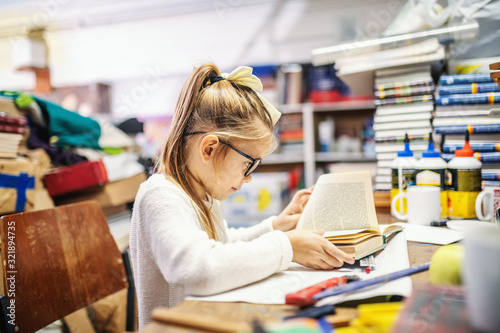 Photographie Adorable caucasian blond girl with ponytail and with eyeglasses sitting in bookstore and reading exciting book