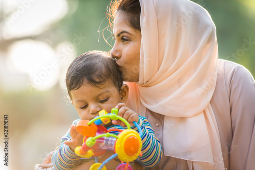 Arabic mom and her little toddler playing outdoors Canvas Print