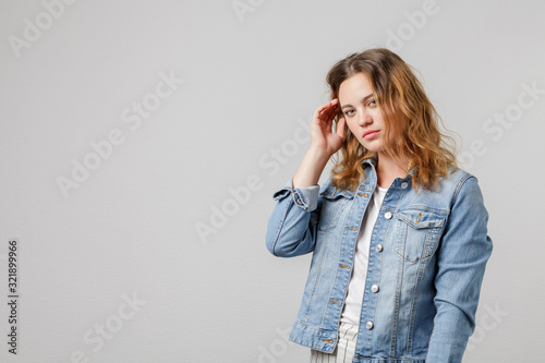 Valokuva Young girl with long flowing hair in a denim looks thoughtfully at the camera and touches her hair