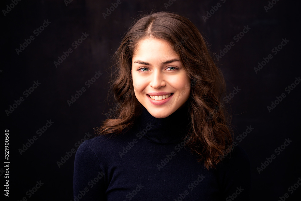 Fototapeta Close-up portrait of attractive young woman at dark background