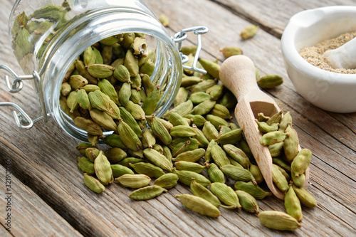 Fototapeta Green aromatic cardamom pods. Jar of whole cardamom pods and mortar of crushed seeds on table. obraz