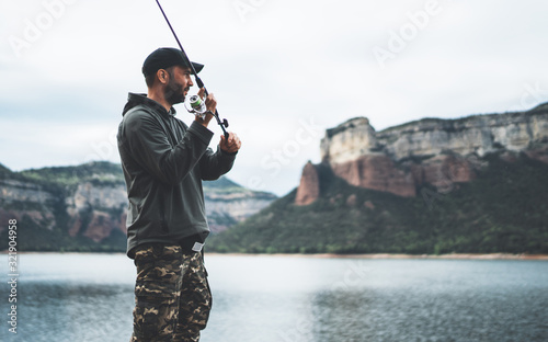 Obraz fisherman enjoy hobby with fishing rod on lake, person catch fish on background mountain, holiday relaxation fishery concept - fototapety do salonu