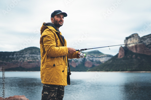 Obraz beard fisherman hold in hands fishing rod, man enjoy hobby sport on mountain river, person catch fish on background nature, relax fishery concept - fototapety do salonu