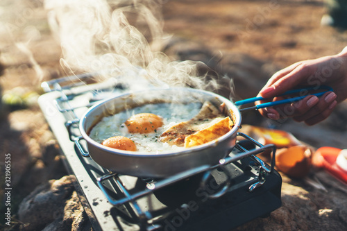 Obraz na plátně person cooking fried eggs in nature camping outdoor, cooker prepare scrambled br