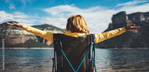 Obraz happy tourist traveler sits with raised hands, girl hiker enjoying mountains lake with arms outstretched breathing of fresh clean air in trip in spain, relax holiday - fototapety do salonu