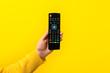 Leinwanddruck Bild - black remote control in hand over yellow background