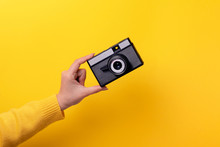 Old Camera In Hand Over Yellow Background