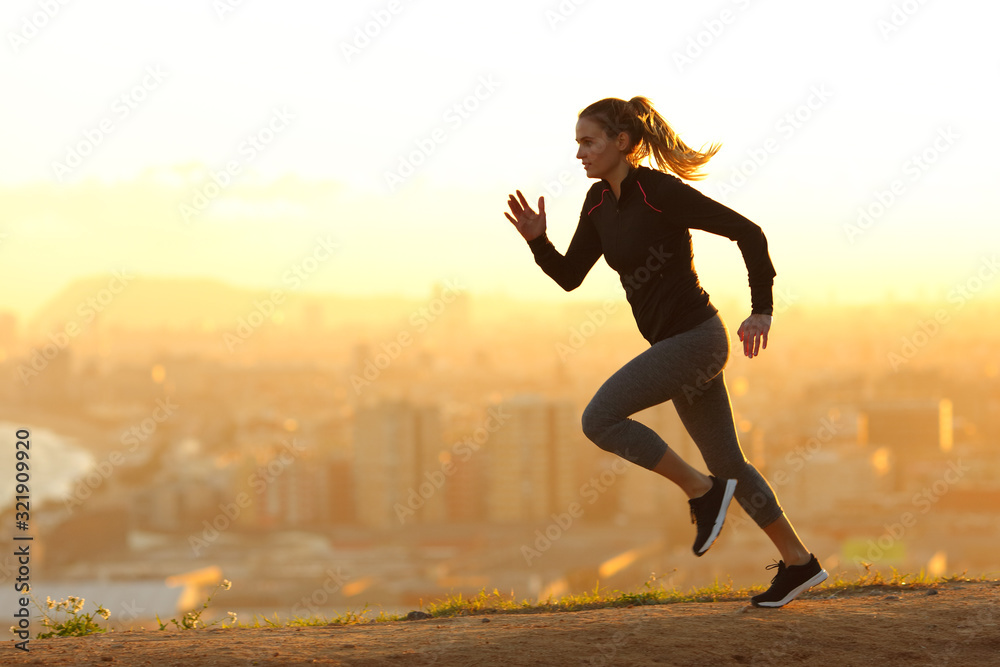 Fototapeta Runner woman running in the outskirts of the city