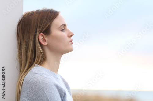 Serious melancholic woman looking away on the beach Canvas Print