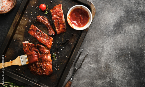 Delicious barbecued ribs seasoned with a spicy basting sauce and served on iron pan Wallpaper Mural