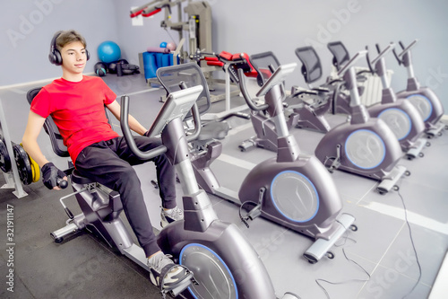 young man in sportswear in the gym on a stationary bike Wallpaper Mural