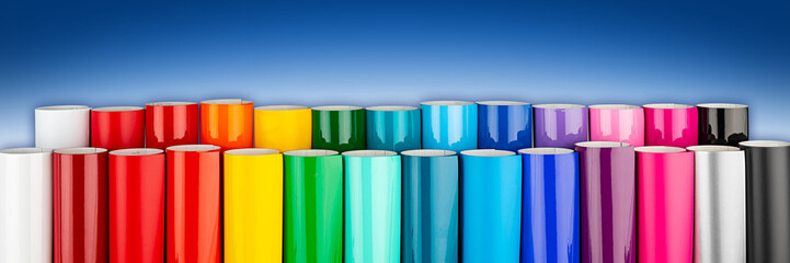 Row of various rainbow colored vinyl car wrapping or plotter cutting sticker foil film rolls blue white wide panorama banner background