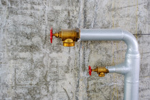 Two Metal Water Pipes Of Industrial Extinguisher System With Brass Valves On Grey Concrete Wall Background On Construction Site