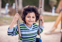 A Smiling Kid Boy On A Swing. ...