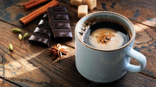 Fototapeta Coffee and spices star anise, cinnamon sticks, cardamom pods and dark chocolate bark on wooden table. Breakfast concept obraz