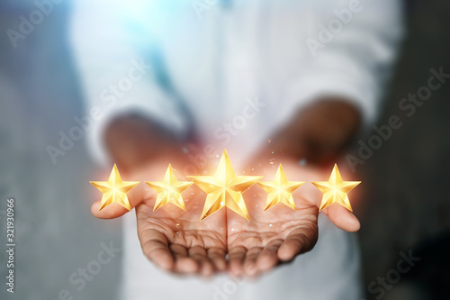 Photo A young man shows 5 stars in the palm of his hand, assigning a new rating, rating services, a new level, business concept