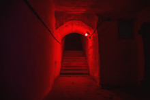 Staircase With Steps In Tunnel Of Underground Military Bunker With Red Light.