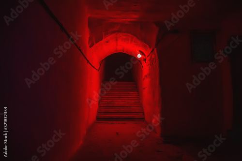 Staircase with steps in tunnel of underground military bunker with red light Fototapeta