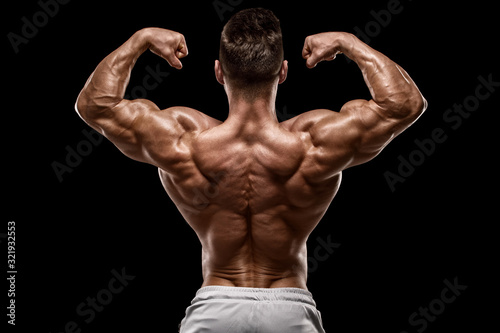 Fotografie, Tablou Muscular man showing back muscles rear view, isolated on black background