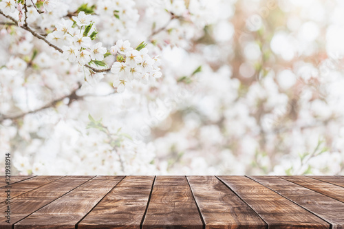 Fototapeta Empty wood table top and blurred sakura flower tree in garden background with vintage filter - can used for display or montage your products. obraz
