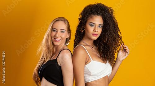 Fototapeta Blonde and brunette women having fun portrait against yellow background