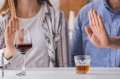 Photo Couple refusing to drink wine and whiskey. Concept of alcoholism