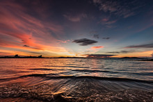 Sunset At The Beach Of Kota Kinabalu, Borneo. Tilt Shift Photography Of The Falling Sun At The Shore Of Sabah, Malaysia. Colorful Red And Yellow Sky With Some Clouds And Small Waves At The Beach