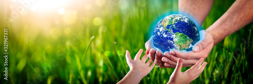 Fotografía Hands Of Man Giving Earth To Child - Protect The Environment For Future Generati