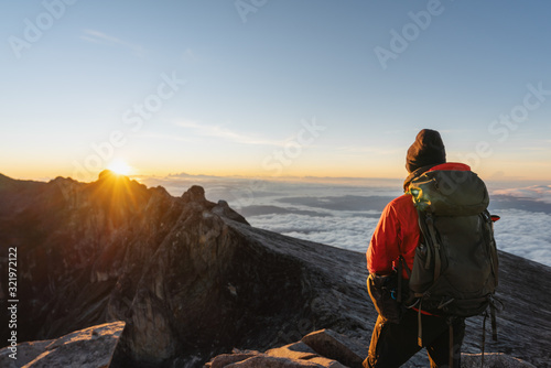 Fototapeta a man with backpack enjoying sunrise over the clouds on Kota Kinabalu summit in Malaysia. Travel lifestyle, adventure and outdoor activity concept obraz