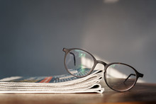 Glasses With Stack Of Newspapers