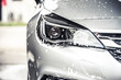 canvas print picture - Manual car wash with white soap, foam on the body. Washing Car Using High Pressure Water.