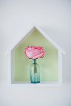 Single Pink Rose In Blue Vintage Bottle. House-shaped Box With Flower Inside.