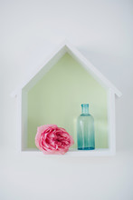 Single Pink Rose And Blue Vintage Bottle. House-shaped Box With Flower Inside.