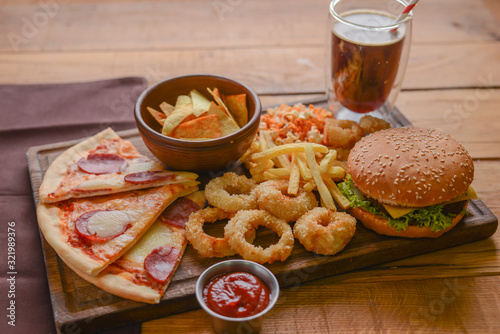 Fast food concept with greasy fried onion rings, burgers, and pizza with french fries and popcorn. Junk food concept. © zhinna