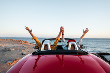 Couple Driving Convertible Car, Traveling Near The Ocean On A Sunset, View From The Backside. Happy Vacations And Traveling By Car Concept