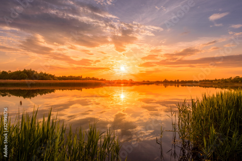 Fototapeta Scenic view of beautiful sunrise or dawn above the pond or lake at spring or early summer morning with cloudy sky background, fog over water and reed grass with dew at foreground. Landscape. Water ref obraz