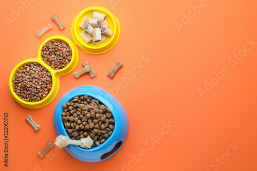 Bowls with dry pet food on color background Wallpaper Mural