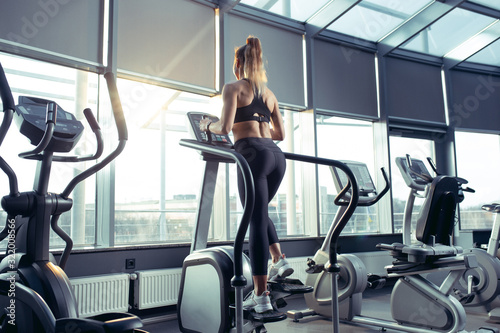 Fotografía Young muscular caucasian woman practicing in gym, doing cardio